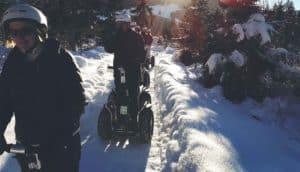 Segway Fahrer im Schnee, im Hintergrund die Sonne