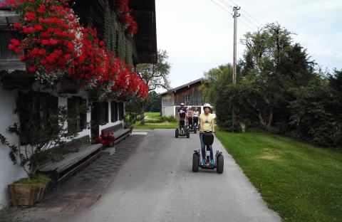 oberbayerisches Bauernhaus mit vielen roten Blumen und eine Gruppe Segway Fahrer