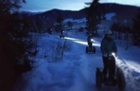 mehrere Segway Fahrer im Schnee mit LED Lampen