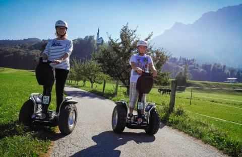 zwei Segway Fahrer im Hintergrund die Kirche St. Nikolai in Ebbs Tirol
