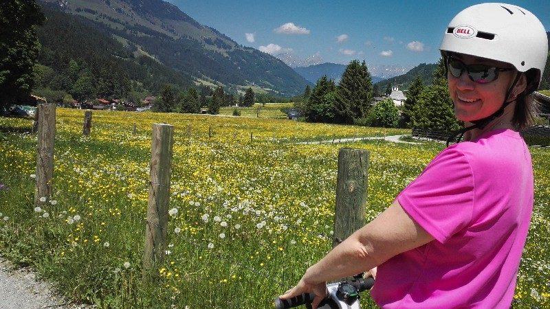 lachende Segway Fahrerin neben blühender Bergwiese in Aschau Tirol