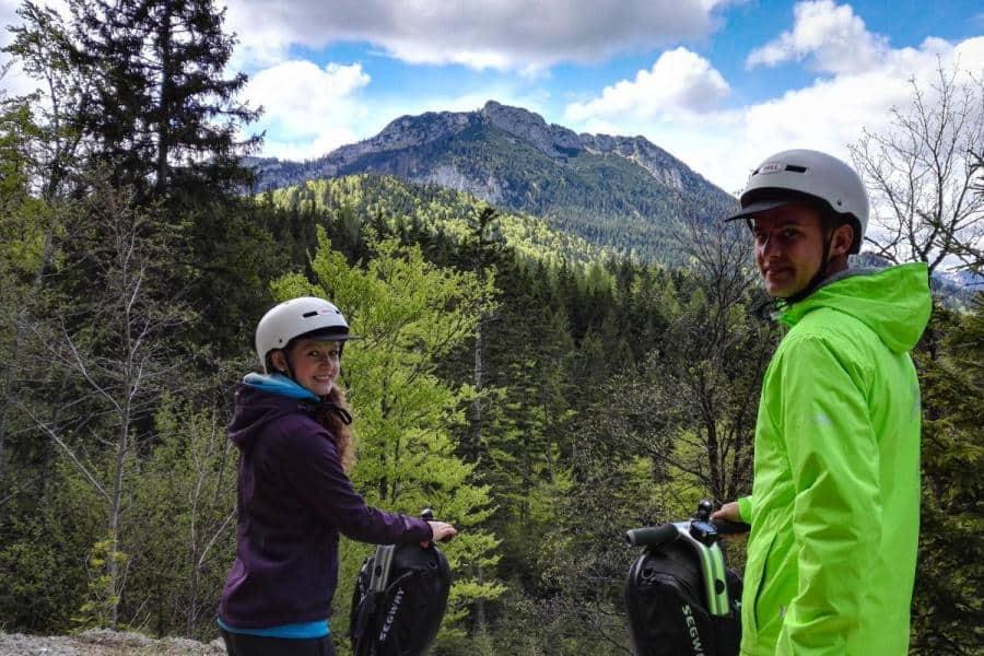 zwei Segway Fahrer mit Helm in den Bergen