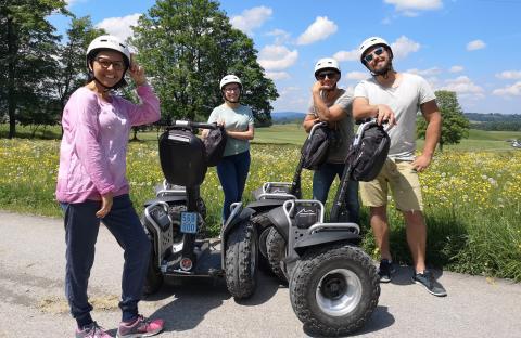 Segway Fahrer Gruppe bei blauem Himmel und Blumenwiese