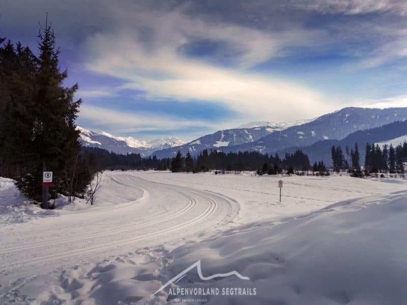 Langlauf Loipe mit verschneiten Bergen im Hintergrund