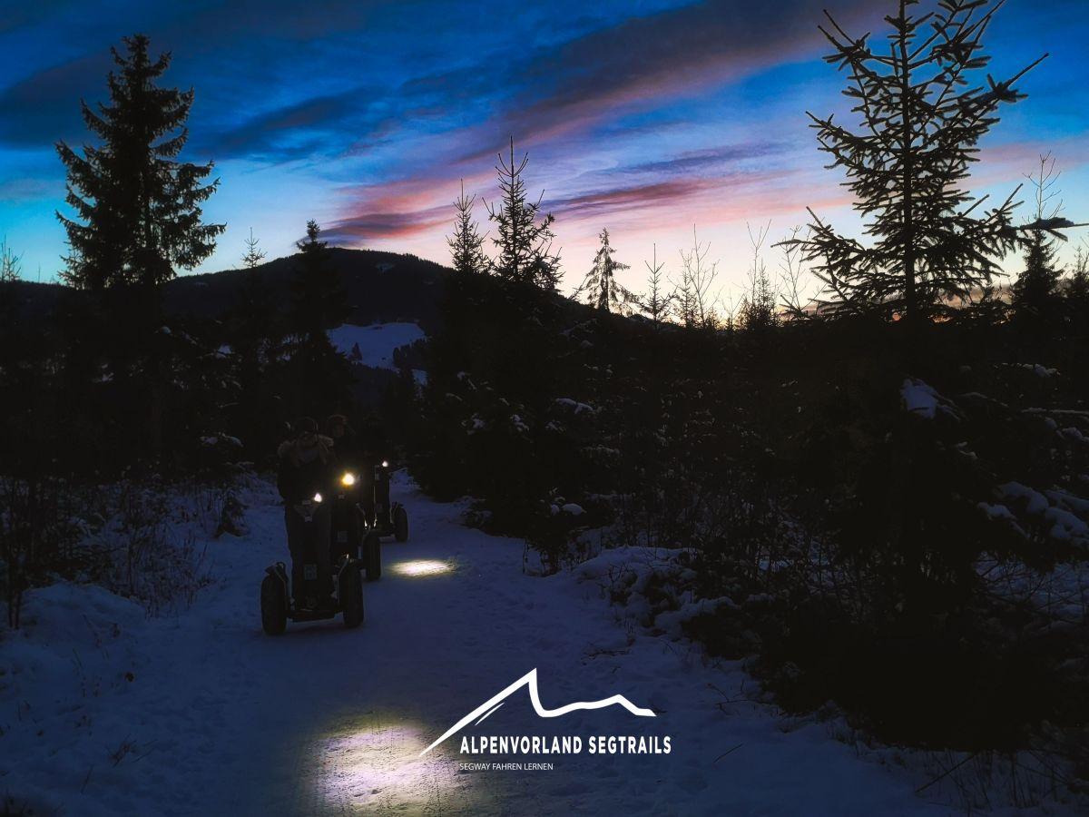 Segway Fahrer mit Licht im dunkeln auf Schnee.