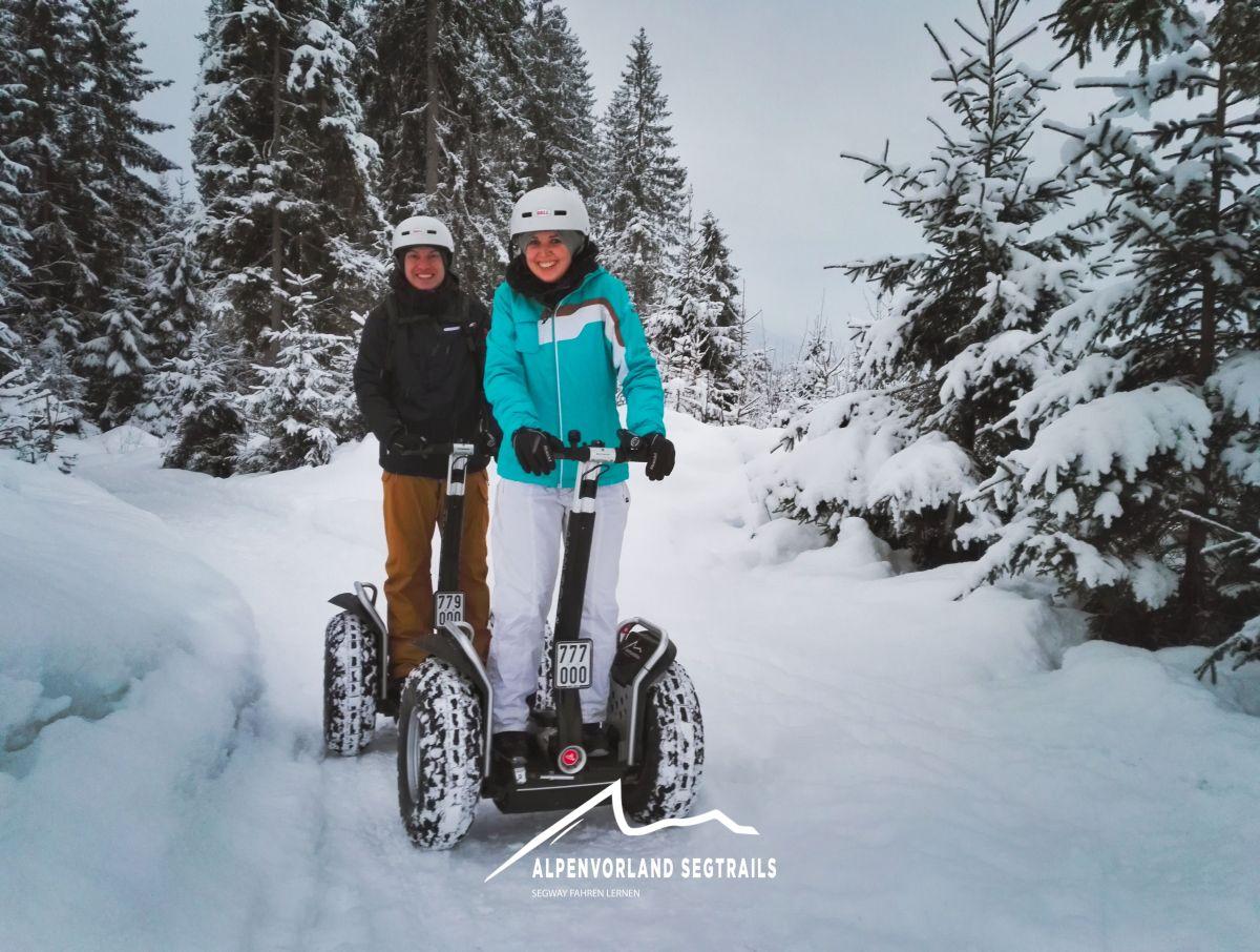 Zwei Segway Fahrer, mit dicker Winterbekleidung im tiefen Schnee